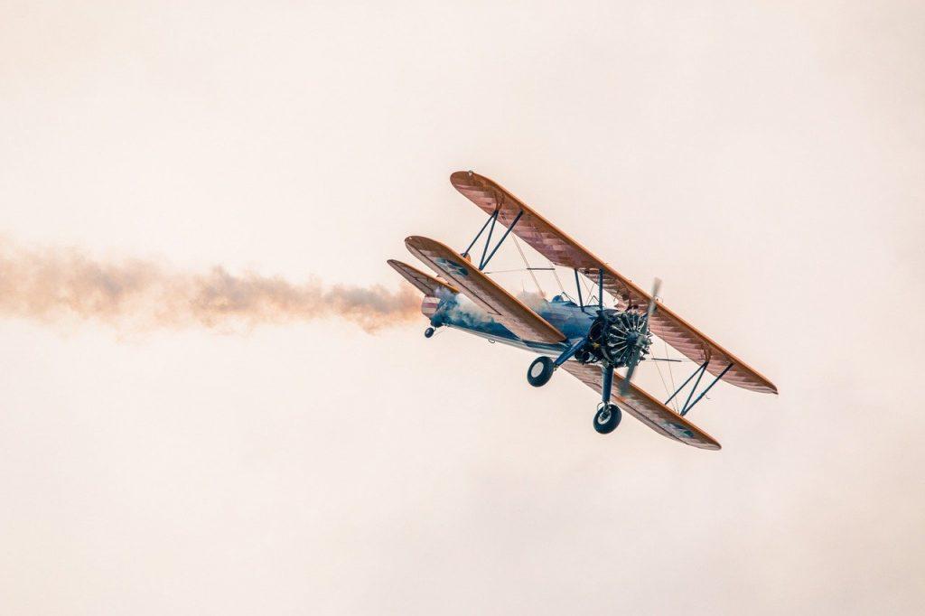 Avión antiguo en vuelo emitiendo contaminación